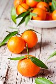 fresh tangerines with leaves on rustic wooden background