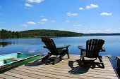 foto of dock a lake  - Two adirondack wooden chairs on dock facing a blue lake with clouds reflections - JPG