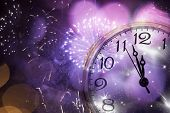 New Year's at midnight - Old clock against fireworks and holiday lights