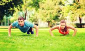 fitness, sport, training and lifestyle concept - couple doing push-ups outdoors
