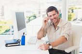 Smiling casual businessman worknig at his desk in his office