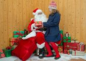 A girl in winter clothing visiting Santa in his grotto