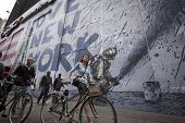 NEW YORK - SEPT 11, 2014: An unidentified couple walk their bikes by a mural that says We Love New York featuring a firefighter spraying water from a hose on the anniversary of the 2001 terror attack.