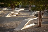 ARLINGTON, VA - SEPT 13, 2014: Granite and stainless steel memorial units and Crape Myrtle trees at the Pentagon Memorial. Each bench has a pool of water and name of each victim of the 2001 attack.