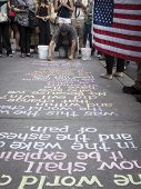 NEW YORK - SEPT 11, 2014: New York City artist Hans Honchar uses colorful chalk to write phrases on the sidewalk near the World Trade Center in Manhattan while someone holds an American Flag.