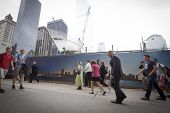 NEW YORK - SEPT 11, 2014: On the anniversary of the 911 attacks, people walk along Vesey St next to the World Trade Center site at 10:28 a.m., the time when the North tower collapsed.