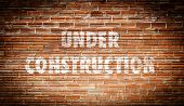The words under construction written on a brick wall