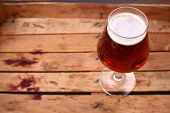 picture of wooden crate  - Glass of amber beer standing in an old dirty wooden crate - JPG