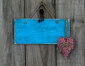 Blank blue wood sign with red heart and iron keys hanging on rustic wooden background