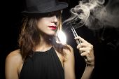 pic of e-cig  - woman smoking or vaping an electronic cigarette to quit tobacco - JPG