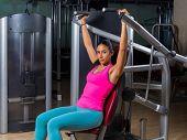 Military press machine woman workout at gym