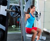 girl squats in multipower squatting smith machine barbell at gym smith