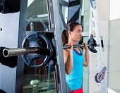 brunette girl in multipower barbell shoulder press Smith machine at gym