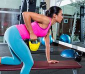 girl one arm kettlebell bent over row on bench workout exercise at gym