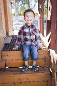 stock photo of caboose  - Cute Young Mixed Race Boy Having Fun Outside Sitting on Railroad Car Steps - JPG