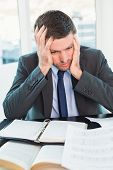 Stressed businessman with head in hands in his office