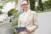 Young businesswoman using tablet pc outside in the city