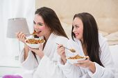 Pretty friends wearing bathrobes eating cereal at home in the bedroom