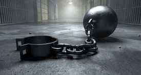 picture of ball chain  - A vintage ball and chain with an open shackle on an old prison cell block floor lit by overhead lights - JPG
