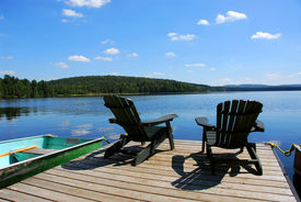 image of dock a lake  - Two adirondack wooden chairs on dock facing a blue lake with clouds reflections - JPG