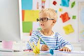 pic of schoolboys  - Portrait of little schoolboy in glasses sitting at the desk - JPG