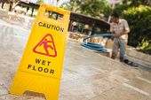 stock photo of stone floor  - Close up yellow caution sign and blur of man doing stone floor polishing - JPG
