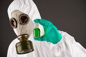stock photo of respiration  - Man in respirator and protective clothing showing a beaker with green liquid - JPG