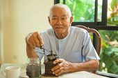 stock photo of wooden box from coffee mill  - Asian senior man with vintage coffee grinder and coffee beans - JPG