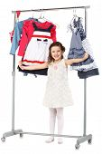 pic of wardrobe  - Little fashionable girl chooses clothes in a wardrobe Isolated on white background - JPG