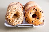 stock photo of serving tray  - Close up Deliciously Baked Bagel Breads for Office Snacks Piled on a White Tray and Served on the Table - JPG