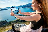 stock photo of sea-scape  - Young woman in dress photographing with digital table sea scape sitting on the mountain top - JPG