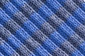 picture of diagonal lines  - Background texture of handmade crochet work in blue and grey with a wavy repeating ridged pattern with weave yarn and fiber detail and diagonal ridged lines full frame close up from above - JPG