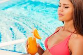 image of woman bikini  - Side view of beautiful young woman in bikini holding cocktail and keeping eyes closed while sitting by the poolEnjoying summer time - JPG