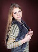 image of vest  - Beautiful blonde in a fur vest on a dark background - JPG