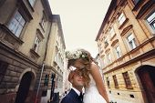 foto of forehead  - bride groom kisses the forehead in the old city Lviv - JPG