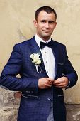 foto of tuxedo  - Handsome groom at wedding tuxedo smiling and waiting for bride - JPG