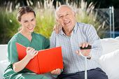 pic of nursing  - Portrait of smiling female nurse and senior man with book at nursing home - JPG