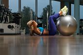 picture of abdominal  - Middle Age Woman Exercising Abdominals On Exercise Ball In Fitness Club - JPG