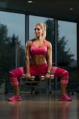 foto of squatting  - Middle Age Woman Performing Dumbbell Squats  - JPG