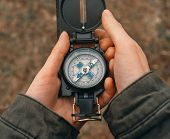 picture of pov  - Female traveler holding a compass on nature - JPG