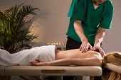 picture of health center  - Chiropractor treating young woman in health center - JPG