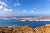 stock photo of canary  - The Island of La Graciosa and the port of Caleta del Sebo taken from the Mirador del Rio a famous viewpoint on Lanzarote in the Spanish Canary Islands - JPG