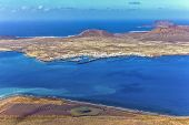 picture of canary  - The Island of La Graciosa and the port of Caleta del Sebo taken from the Mirador del Rio a famous viewpoint on Lanzarote in the Spanish Canary Islands - JPG