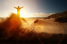 image of prayer  - Silhouette of a man with hands raised in the sunset on a beach concept for religion - JPG