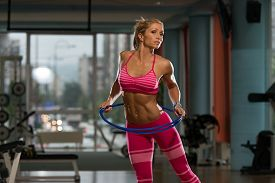 stock photo of hulahoop  - Middle Age Womane Playing Around With Hula Hoop Rings  - JPG