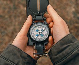 stock photo of pov  - Female traveler holding a compass on nature - JPG