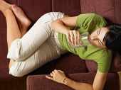 Agua potable de mujer en sofá
