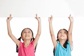 stock photo of identical twin girls  - Happy Asian twins girls with white blank banner over head on white background - JPG