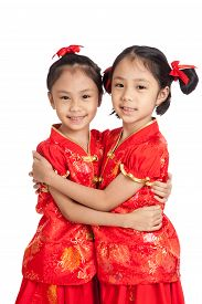 picture of identical twin girls  - Happy Asian twins girls in chinese cheongsam dress isolated on white background - JPG