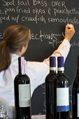 waitress writing menu on menu board, wine bottles in foreground, labels cloned out, focus on foregro